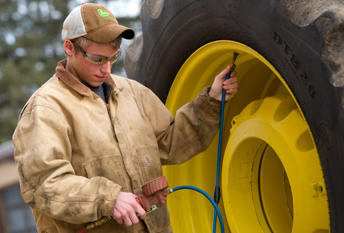 Image of boy putting air in tractor tire